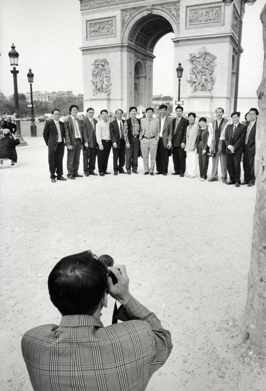 Tourist being photographed in fron of the Arc de Triomphe