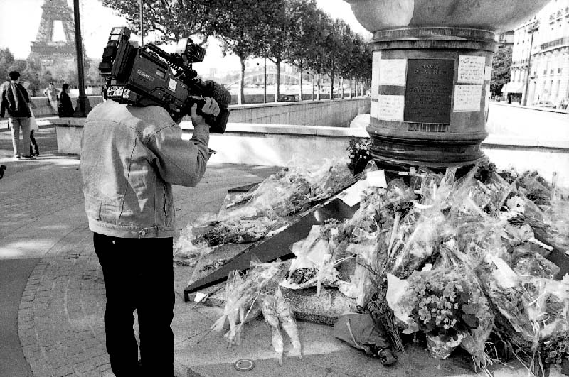 Filming the flower tributes left at The Liberty Flame