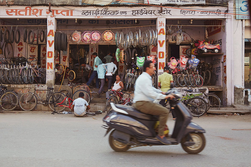 Scotter passing bike shop