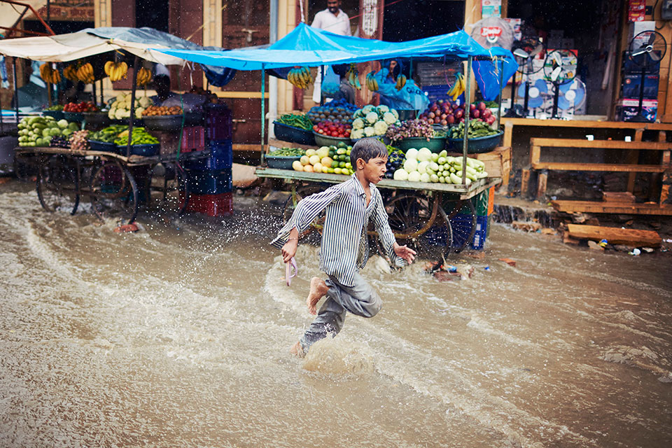 Indian boy running trough monsoon rain